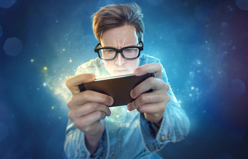 A young man wearing glasses looking at his phone intensely